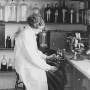 Black and whit image of woman scientist sitting at lab