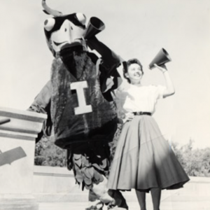 Black and white image of original Cy with early cheerleader