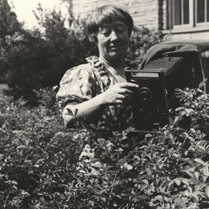 Black and white image of Ada Hayden in a bush taking a photo of the plant