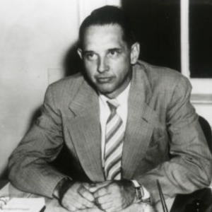 Black and white image of John Vincent Atanasoff sitting at his desk