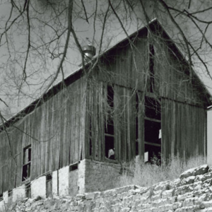 Black and white image of a barn partially dilapidated barn