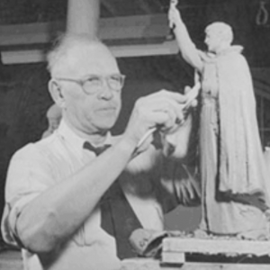 Black and white image of Christian Petersen sculpturing a small statue