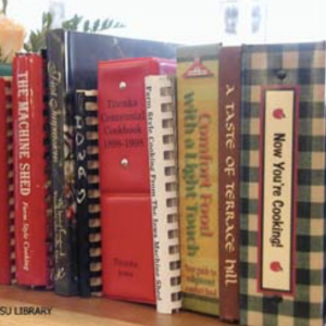 Color photo of a row of cookbooks sitting on a shelf