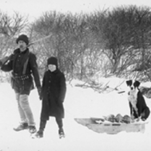 Black and white winter image of two kids standing with a dog sitting a sled