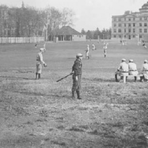 Black and white image of baseball athletes playing the game with Beardshear far in the back