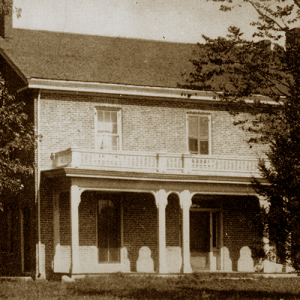 Early photo of the Farm House on the Iowa State University campus in summer.