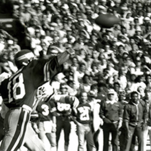 Black and white image of football player throwing a football in front of full stadium behind c. 1970's