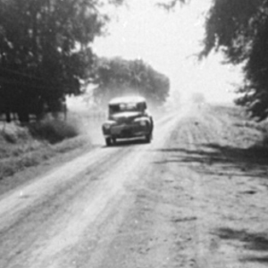 Black and white photo of older vehicle driving down a tree-lined country road churning up dust in the background.